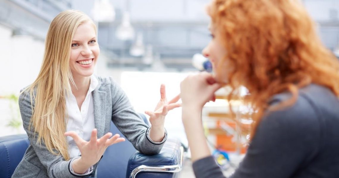 Portrait of young smiling businesswomen speaking to her colleague in office
