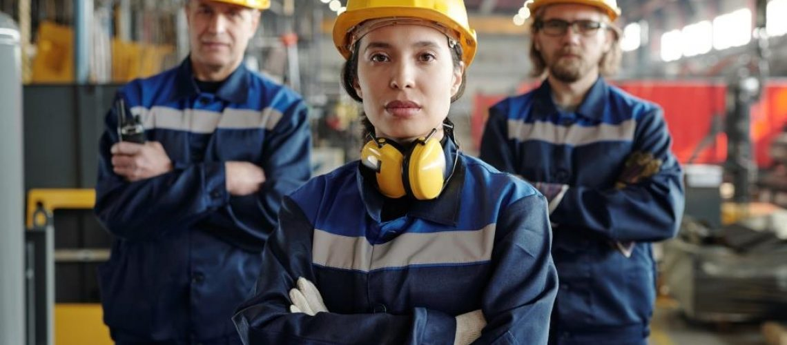 Portrait of serious young woman in hardhat and noise-cancelling headphones working with male colleagues at factory