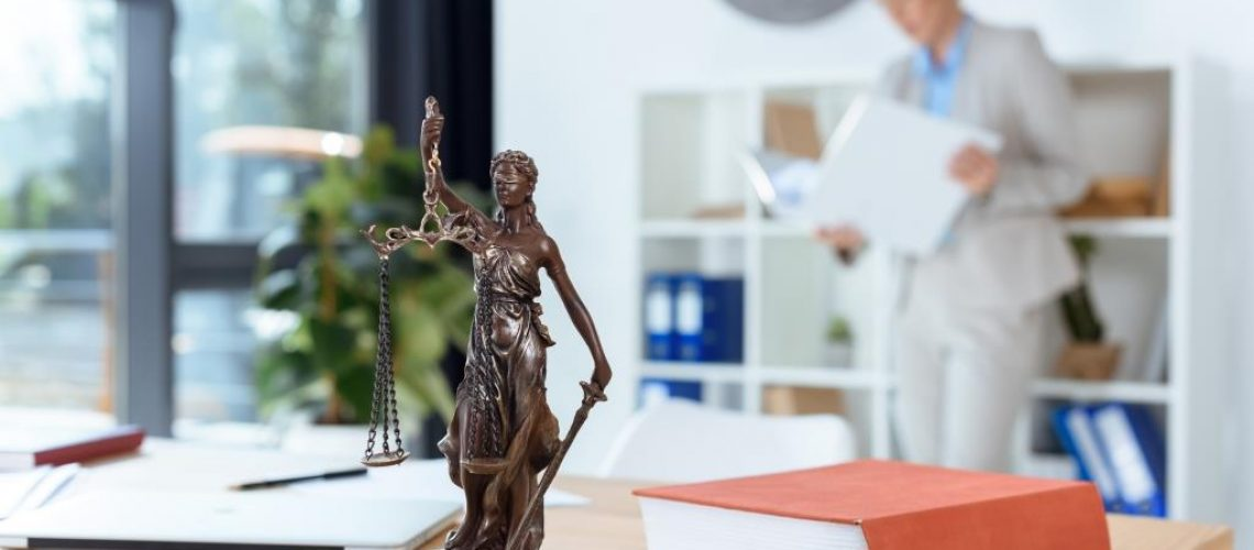 bronze themis sculpture on female lawyer table