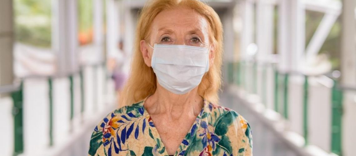 Portrait of blonde senior woman wearing mask for protection from corona virus outbreak at the footbridge in the city outdoors