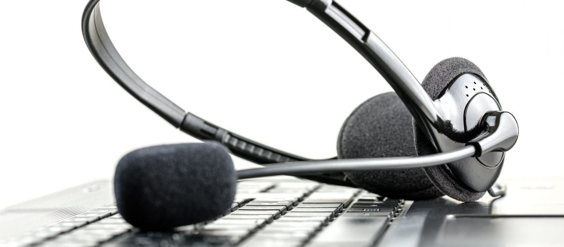 26901768 - headset lying on a laptop computer keyboard conceptual of telemarketing, call center, client services or online support.