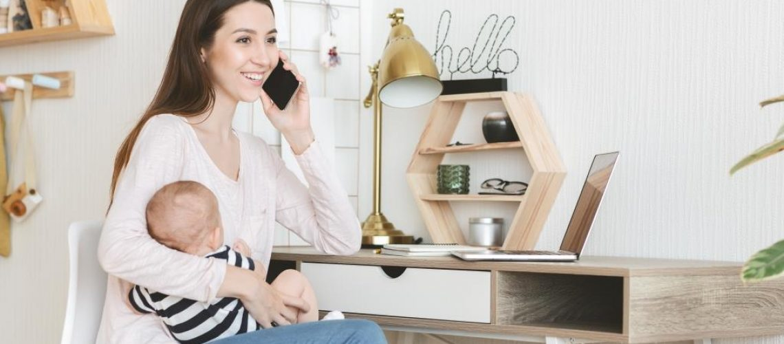 Young mother's lifestyle concept. Smiling mom talking on phone, holding baby in arms and using laptop at home.