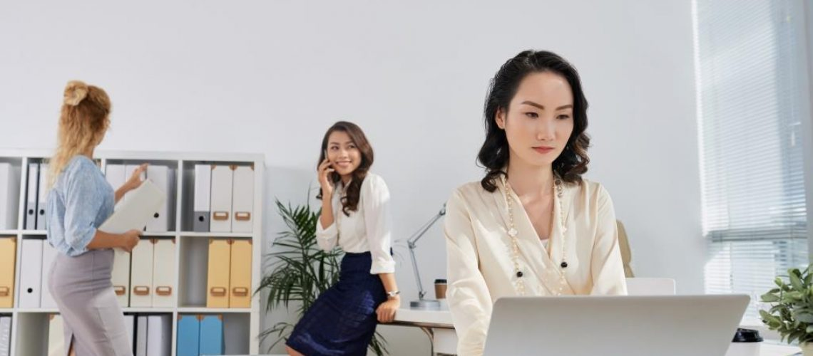 Pretty Chinese business lady working on laptop in office